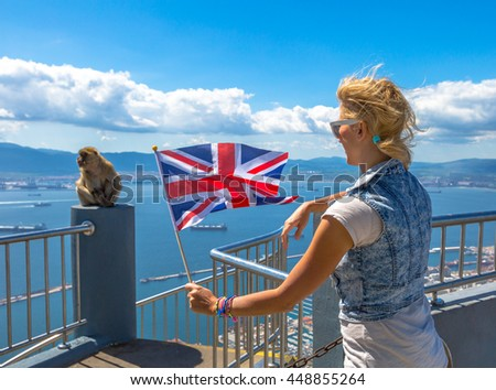 Tourist woman holding an English flag observes one of the famous monkeys of Gibraltar from the top of Gibraltar Rock, in the Upper Rock Natural Reserve. - stock photo