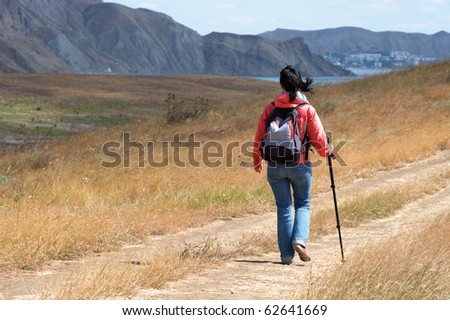 Tourist woman in mountains by the sea - stock photo