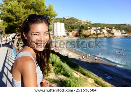 Tourist woman on beach summer vacation in Mallorca (Majorca). Asian lady smiling at camera in Sant Elm (San Telmo) in Andratx, Balearic Islands, Mediterranean sea, Spain, Europe. - stock photo