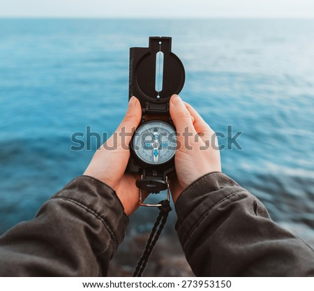 Tourist woman searching direction with a compass on stone coastline near the sea, close-up. Point of view shot. - stock photo