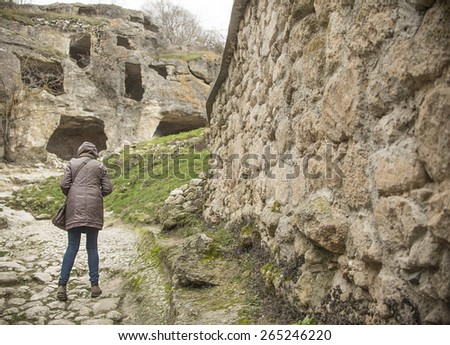 tourist woman stand near old retro vintage aged historical stone wall texture Back view full length girl walk along history fence Empty copy space for inscription  - stock photo