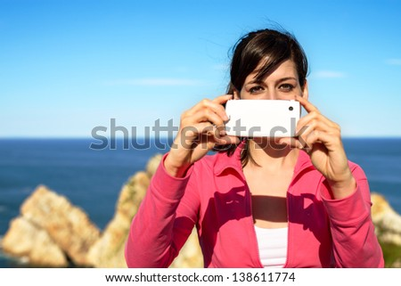 Tourist woman taking photo with cellphone and having fun on summer travel. Brunette girl smiling and taking snapshot on coast landscape.