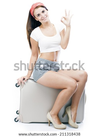 Tourist woman with suitcase giving thumbs up sign isolated white