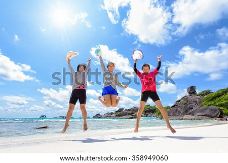 Tourist women three generation family jumping for happy on beach near the sea under the sky clouds and sun of summer at Similan Island in Mu Ko Similan National Park, Phang Nga province, Thailand - stock photo