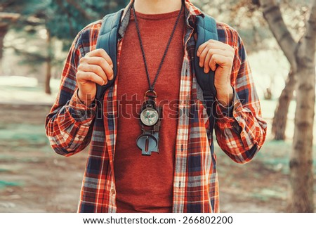 Tourist young man with backpack and compass walking in summer forest - stock photo