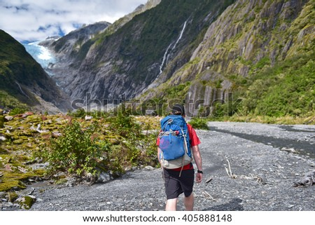Tourist young man with bag and in hat walking in Franz Josef Glacier, New Zealand South Island - stock photo