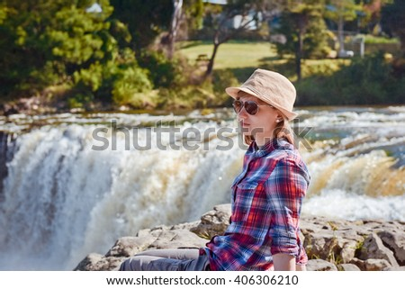 Tourist young woman in hat sitting and looking on the waterfall, New Zealand