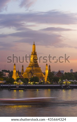 Touristic boat crossing the chao praya river in fron of the Wat Arun, The Temple of Dawn, at sunset, Bangkok, Thailand. 