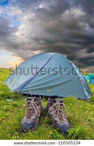 touristic boots near a tent - stock photo