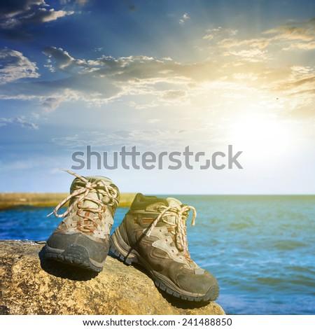 touristic boots on a stone near a sea coast - stock photo