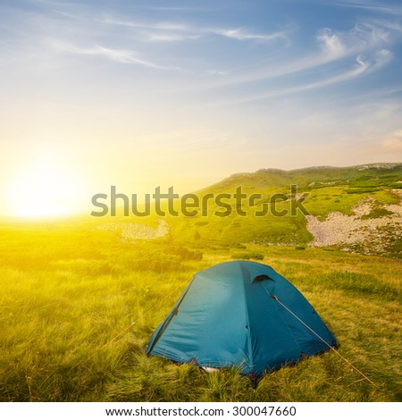 touristic camp in a mountains at the sunset - stock photo