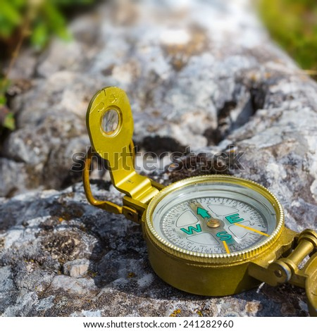 touristic compass on a stone - stock photo
