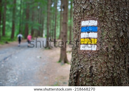 Touristic sign/mark on tree next to touristic path (female tourist in background) - stock photo