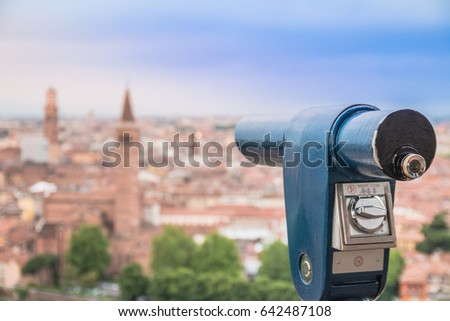 Touristic telescope and blurred city on background. Verona - view from castle San Pietro. A view of the city from the top. Selective focus. Sunrise. Verona, Italy.