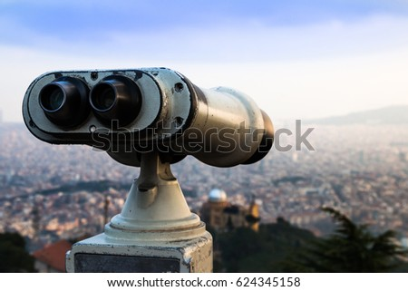 Touristic telescope look at the city with view of Barcelona Spain, close up old metal binoculars on background viewpoint overlooking city. Retro toned photo. Barcelona Tibidabo