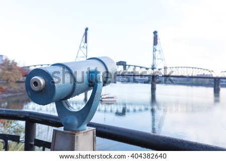 touristic telescope with bridge on tranquil water in gloomy sky in portland