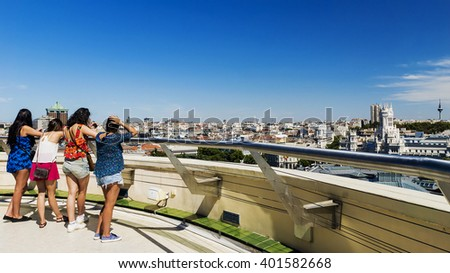 Tourists admire the panoramic view of Madrid from the roof of a tall building - stock photo