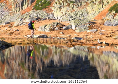 Tourists and mountains near glacier lake reflected by calm waters - stock photo