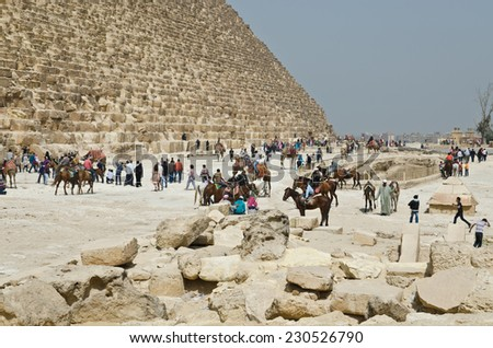 Tourists are near ancient Egyptian pyramids. The Giza Necropolis has been a popular tourist destination since antiquity. - stock photo