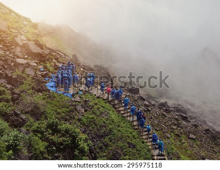 Tourists are walking up a stairway to Niagara Falls with wet water mist and blue raincoats on for a travel or nature concept. - stock photo