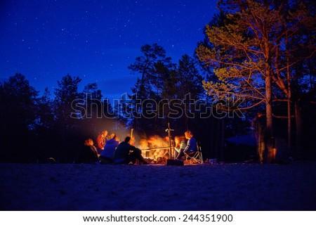 Tourists around the campfire at night. Olkhon Island Lake Baikal. - stock photo