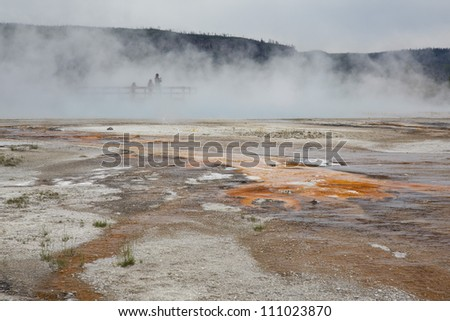 Tourists, barely visible, standing in the sulfite smelling smoke in hot springs in Yellowstone National Park, Montana, Wyoming, USA - stock photo