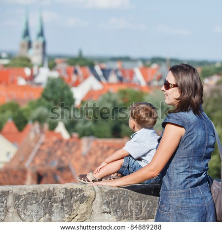 Tourists. Beautiful mother and son walking in europe city. - stock photo