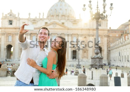 Tourists couple by Vatican city and St. Peter's Basilica church in Rome. Happy travel woman and man taking selfie photo picture on romantic honeymoon in Italy. - stock photo
