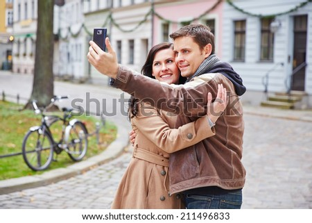Tourists couple taking photo with smartphone in a city