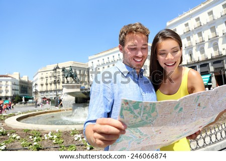 Tourists couple with map in Madrid. Sightseeing people looking at map for tourist attractions and famous landmarks while visiting Puerta del Sol in Madrid, Spain. Multiracial couple. - stock photo