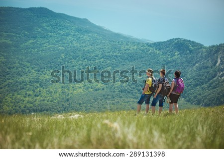 tourists enjoying view from top of a mountain - stock photo