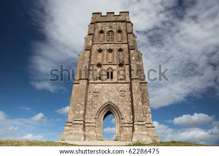 Tourists exploring the ruins of St. Michael's Tower at the top of glastonbury tor in sommerest england