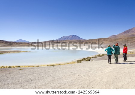 Tourists family visiting Laguna Honda, Bolivia, Antiplano - stock photo