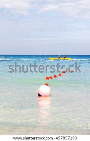 Tourists float on a banana shaped inflatable boat. Active sports leisure. Varadero sandy beach at sunny day. Cuba.