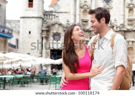 Tourists - happy couple in Cuba. Havana having fun during travel. Young interracial couple, Asian woman, Caucasian man, Plaza de la Catedral, Old Havana. - stock photo