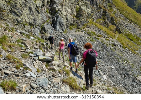 Tourists hiking into a gorgeous landscape in rocky mountains