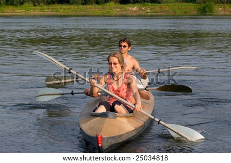 tourists in canoe kayaking across the river - stock photo