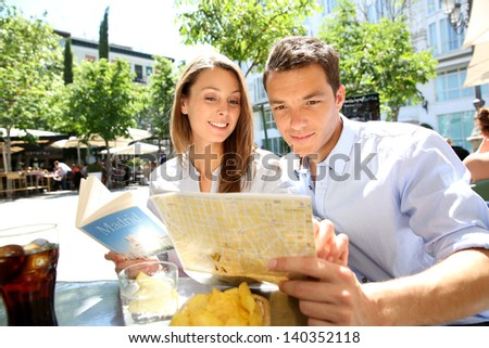 Tourists in Madrid reading city map - stock photo