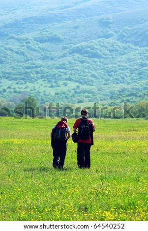 Tourists in mountain meadow. Element of design. - stock photo