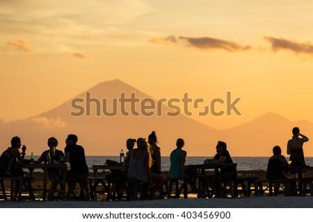 Tourists in the restaurant on Gili Travangan island enjoying evening sunset view on Gunung Batur volcano on Bali, Indonesia. - stock photo