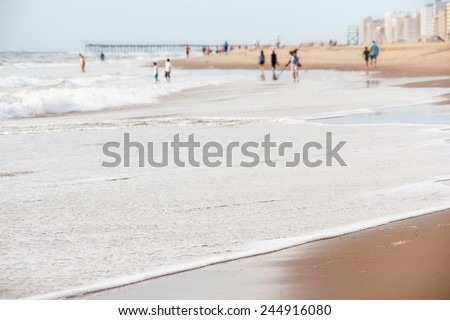 Tourists in the water at Virginia Beach with pier and hotels on beachfront property on a summer day - stock photo