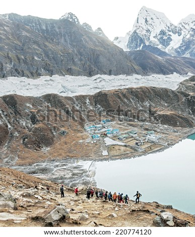 Tourists look at the Gokyo Ri in the glacier, village, and the third lake - Nepal, Himalayas - stock photo