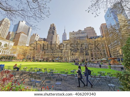 Tourists looking at Green Lawn and Skyscrapers in Bryant Park in Midtown Manhattan, New York, USA. - stock photo