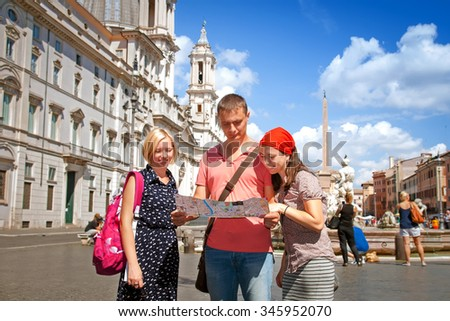 Tourists looking at the map of Rome in Navona square in Rome, Italy - stock photo