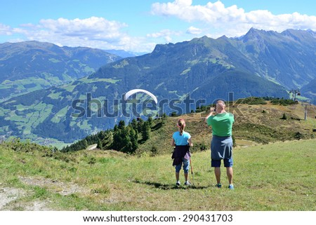 Tourists looking to paraglider flying over beautiful mountains and valley in Mayrhofen, Austria on August 28, 2014.