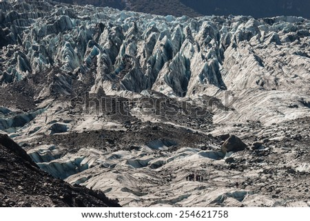 tourists on Fox Glacier in Westland National Park, New Zealand - stock photo