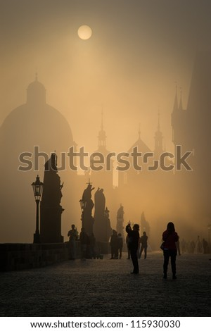 Tourists on Prague Charles Bridge during golden misty morning - stock photo