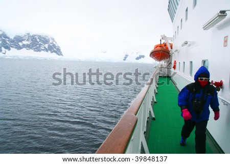 Tourists on promenade deck of cruise ship, watching glaciers, Erreras Channel, Antarctica - stock photo