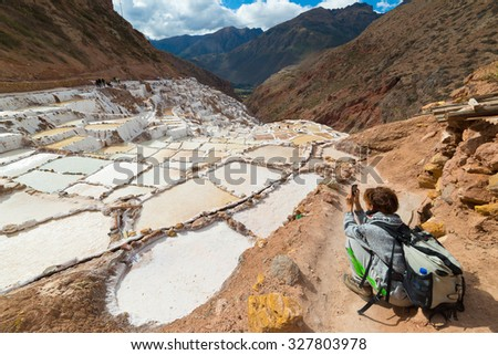 "Tourists photographing white salt pans (""Salineras de Maras"") with smartphone, among the most scenic travel destination in Cusco Region, Peru. Concept of sharing travel moments with new technologies. - stock photo"