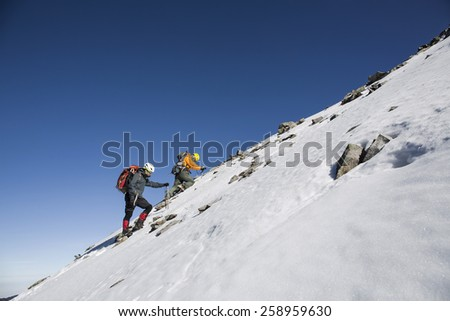Tourists reaches the top of a snowy mountain at sunny winter day.